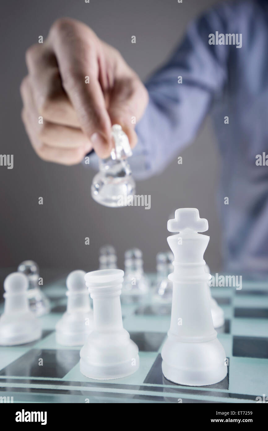 Close-up of man's hand going for checkmate while playing chess, Bavaria, Germany - Stock Image
