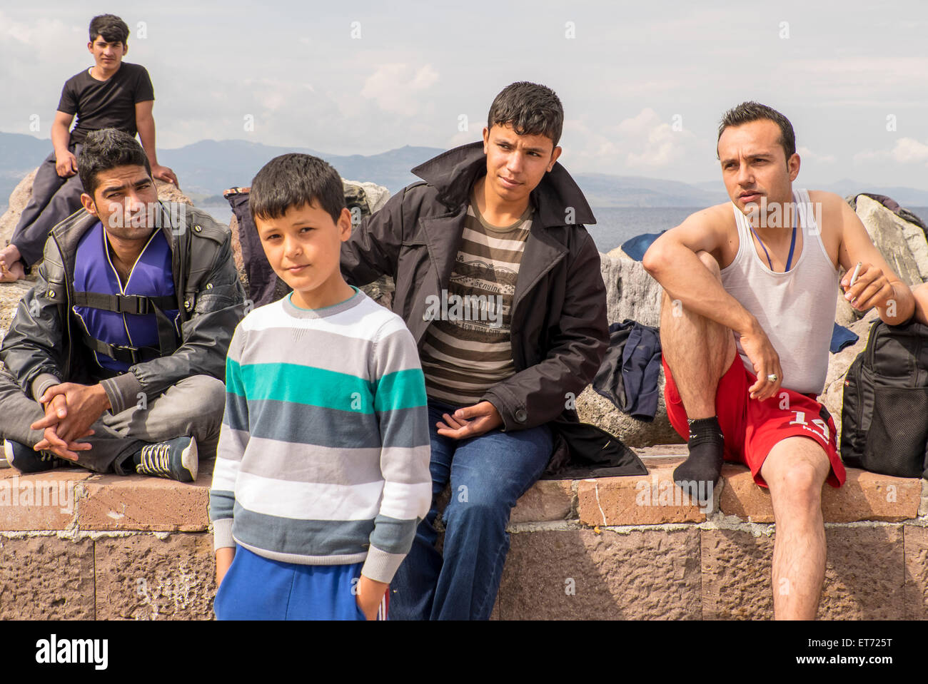 Five Syrian refugees dry off in Molyvos harbor after crossing from Turkey to Greece in rubber rafts. Stock Photo