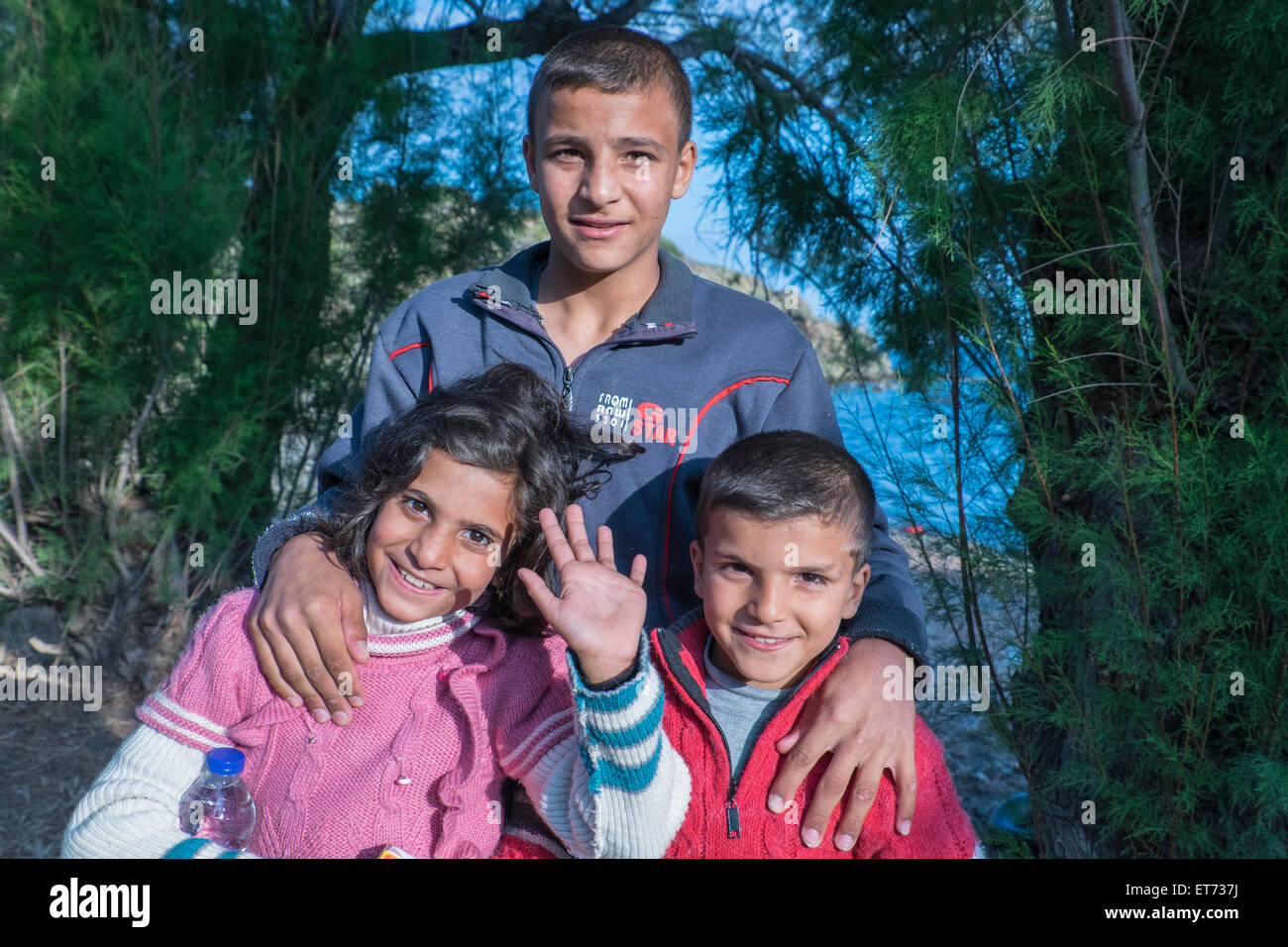 Three Syrian refugee children smile as they arrive in Greece from Turkey in a rubber boat that landed on a Greek - Stock Image