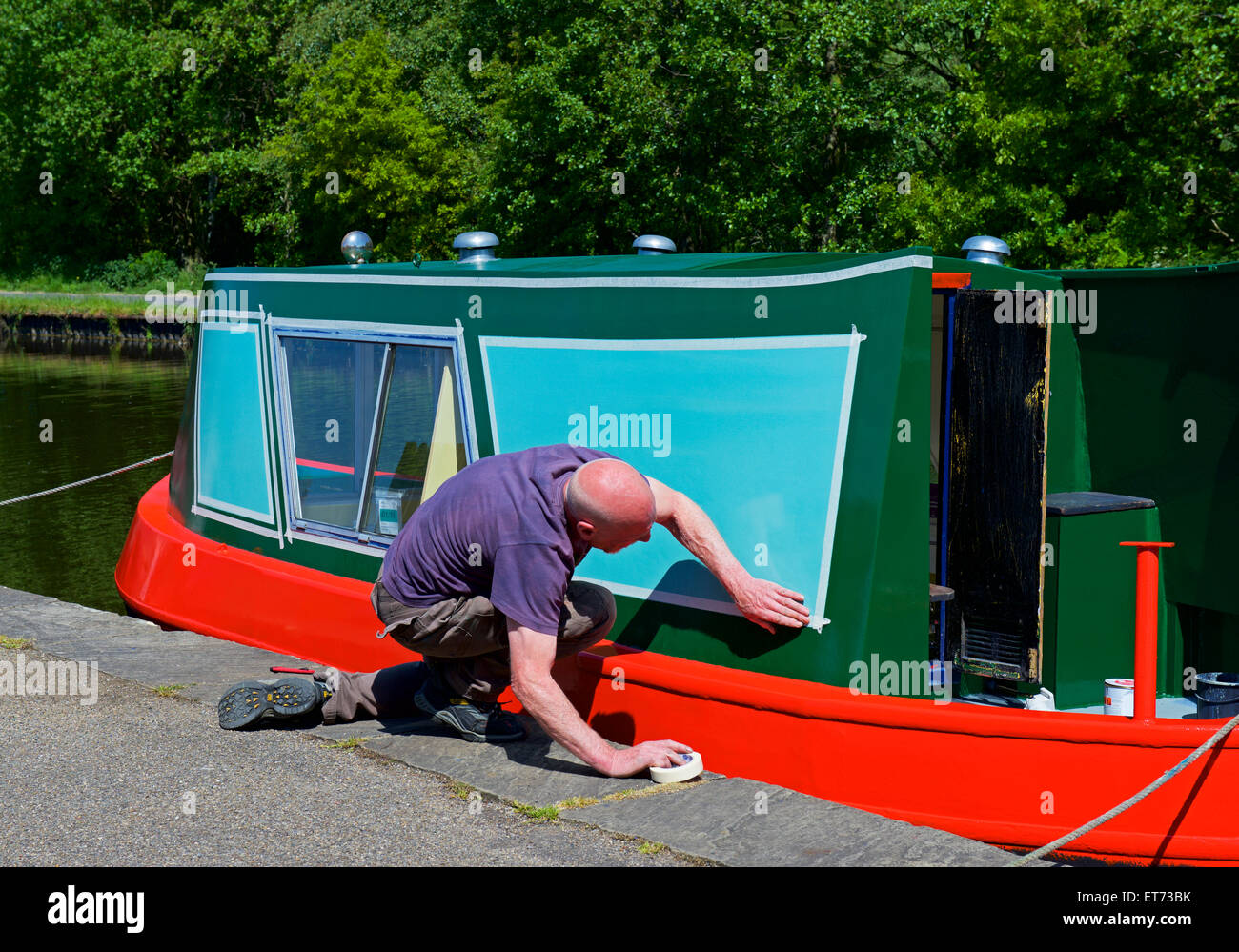 Man preparing narrowboat for painting, Leeds-Liverpool Canal, West Yorkshire, England UK - Stock Image
