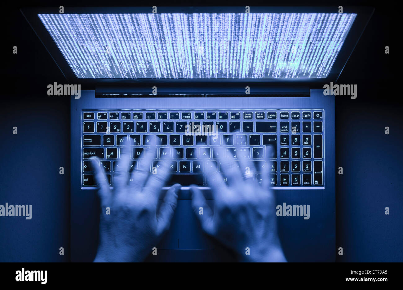 Hands are typing on a laptop computer in the dark with illuminated keyboard and mystic program code on screen - Stock Image