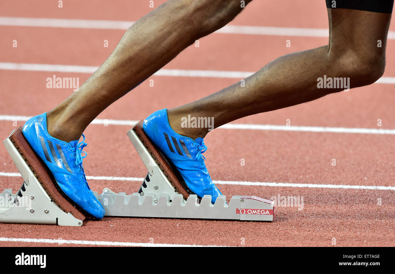 A male athlete (African ethnicity) is getting ready at the starting block on an athletics race track just before - Stock Image