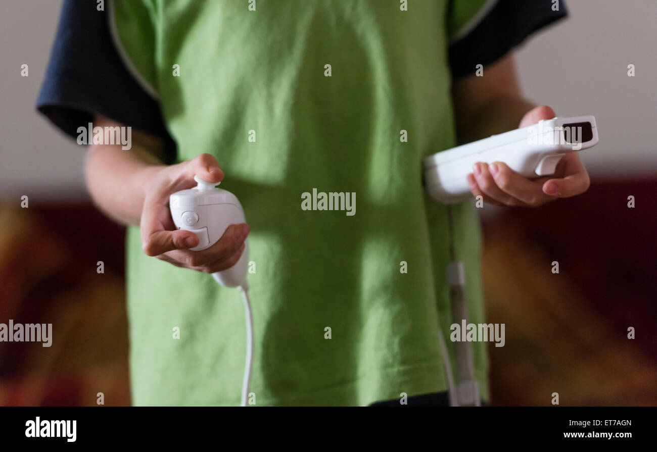 Boy at home holding Nintendo Wii computer game controller. - Stock Image
