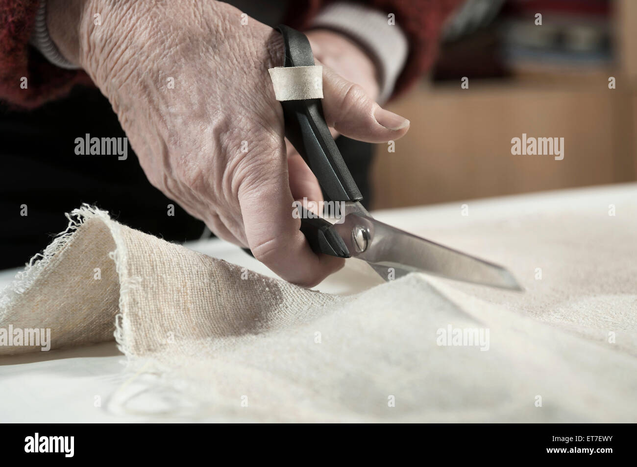 Senior female fashion designer cutting fabric with scissors in workshop Bavaria Germany - Stock Image