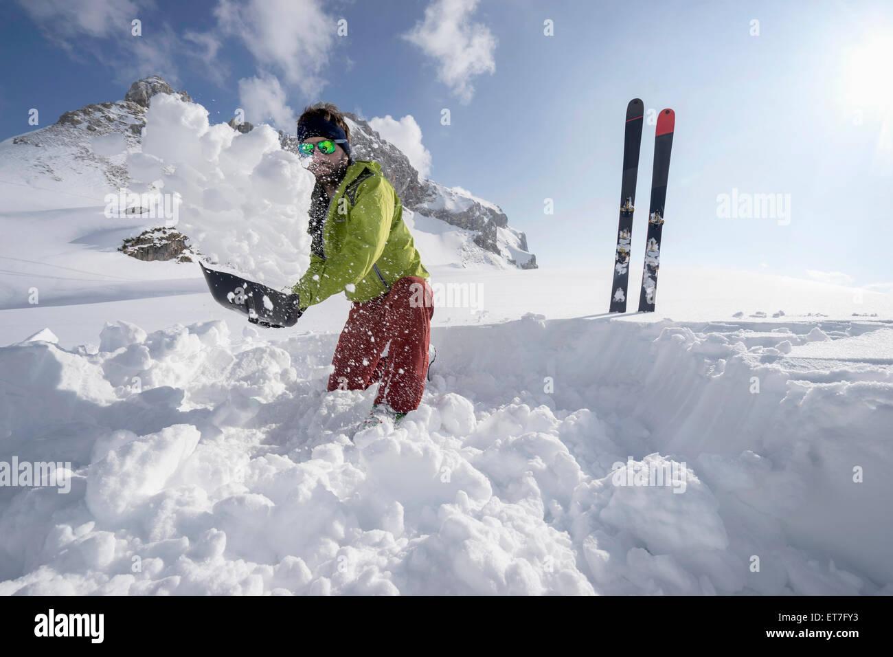Man shovelling snow for bivouac camp, Tyrol, Austria - Stock Image