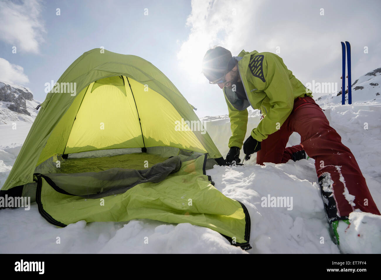Man constructing tent in snow, Tyrol, Austria - Stock Image