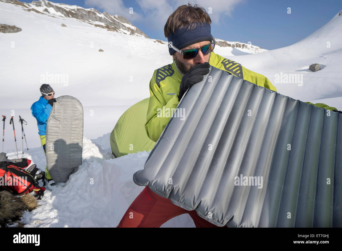 Two men blowing into air mattresses for camping, Tyrol, Austria - Stock Image