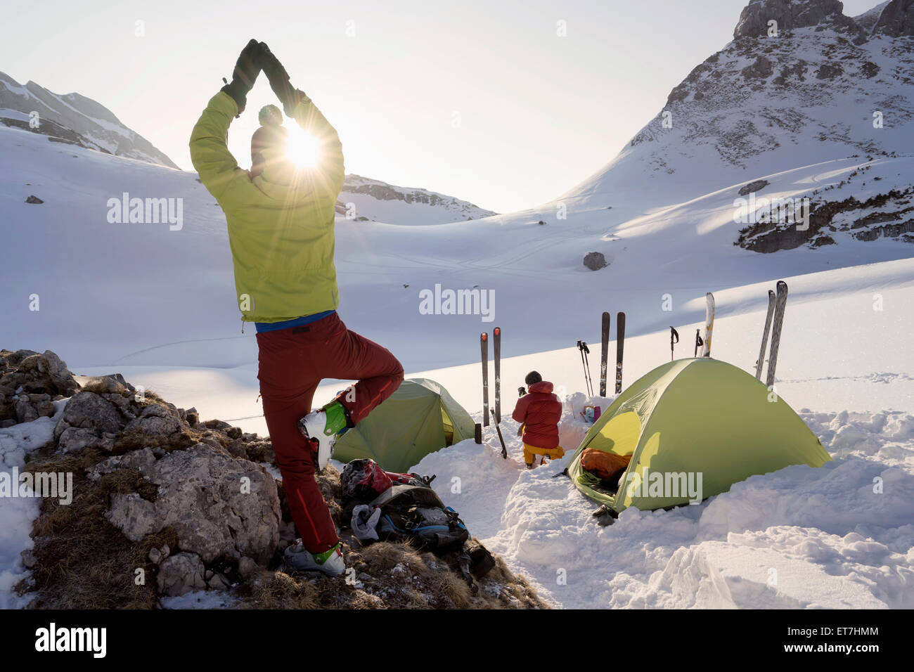 Rear view of man doing yoga at sunrise while camping on mountain, Tyrol, Austria - Stock Image