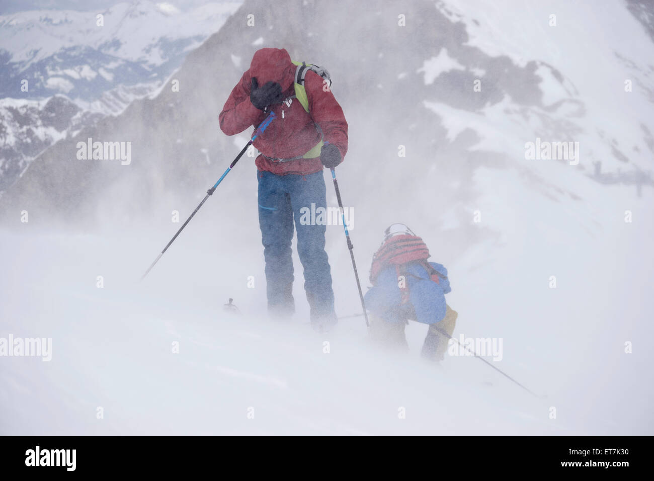 Ski mountaineers climbing on snowy mountain in snow storm, Zell Am See, Austria - Stock Image