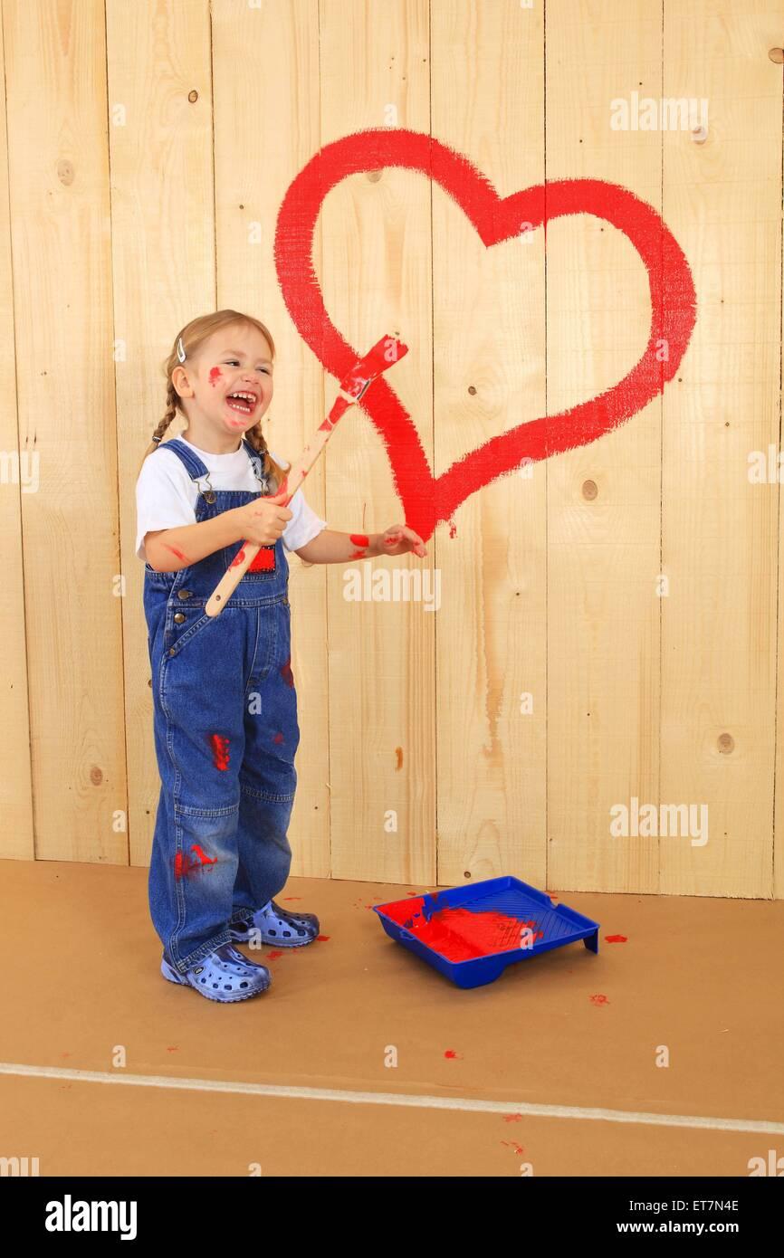 kleines Maedchen steht mit Pinsel lachend vor Bretterwand, auf die sie mit roter Farbe ein Herz gemalt hat   laughing - Stock Image