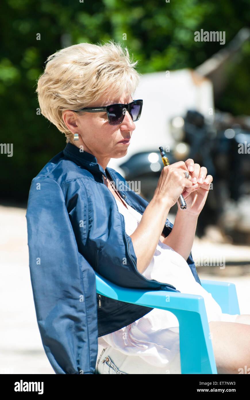 Woman vaping electronic cigarette - Stock Image