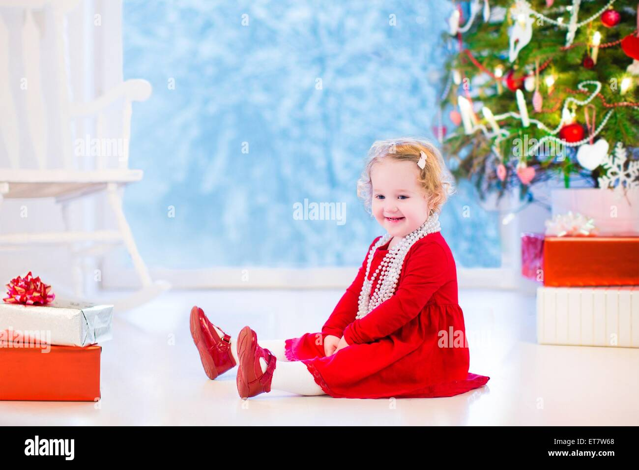 Cute curly little girl in a red dress and white pearl necklace playing under a Christmas tree with presents sitting - Stock Image