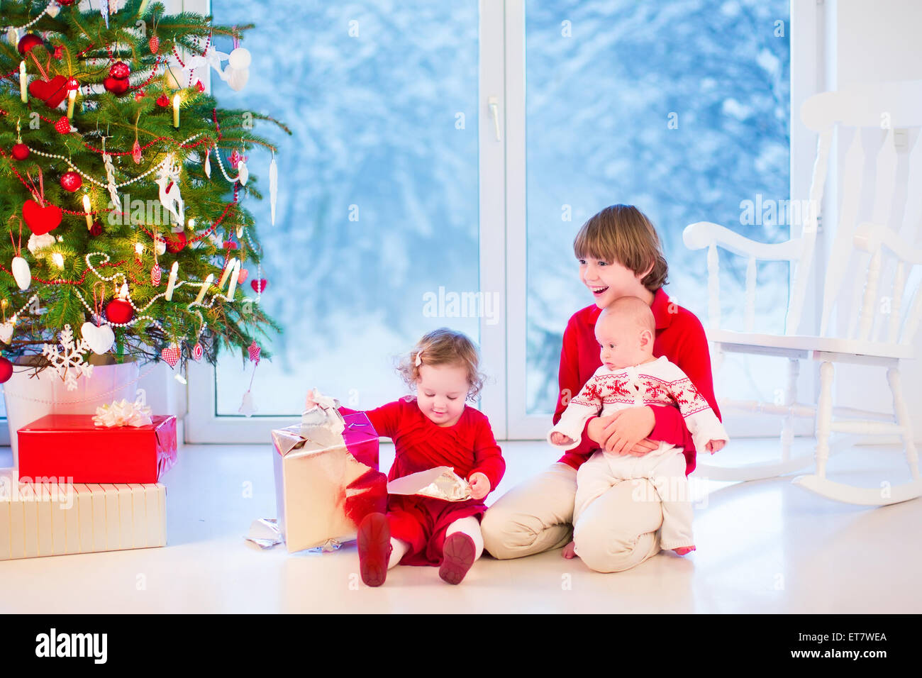 Three kids opening Christmas presents, enjoying Xmas morning in a living room with decorated tree and window into Stock Photo