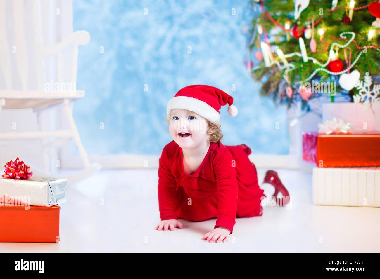 e478aebcfecf Cute curly little girl in a red dress and Santa hat playing under a  Christmas tree
