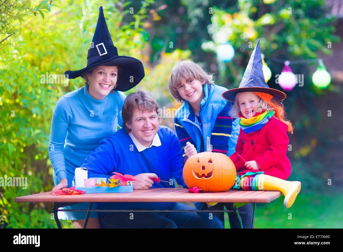 Happy family, parents with two children wearing witch costume and hat celebrating Halloween and pumpkin carving - Stock Image
