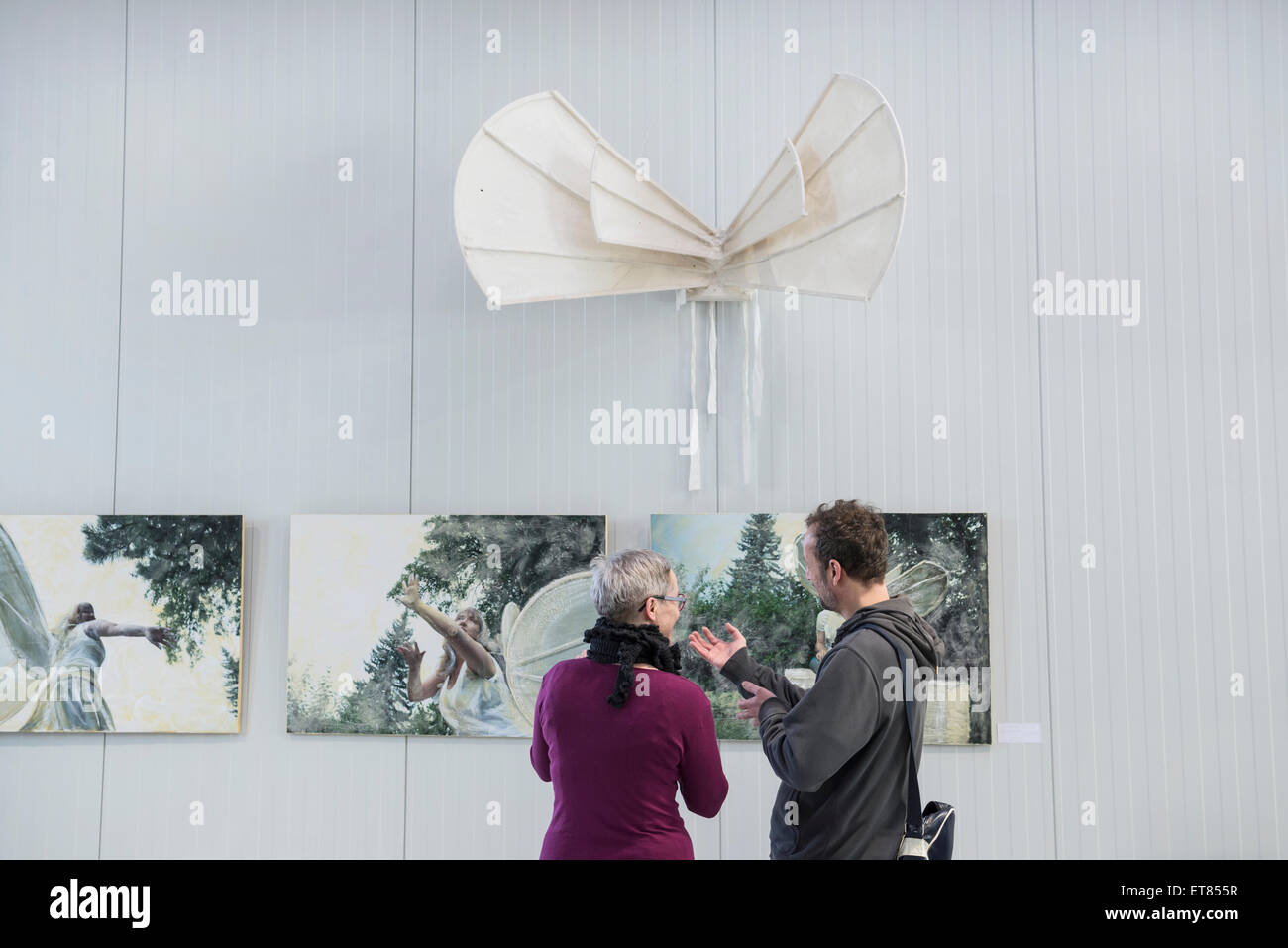 Visitors looking at paintings in an art gallery, Bavaria, Germany - Stock Image