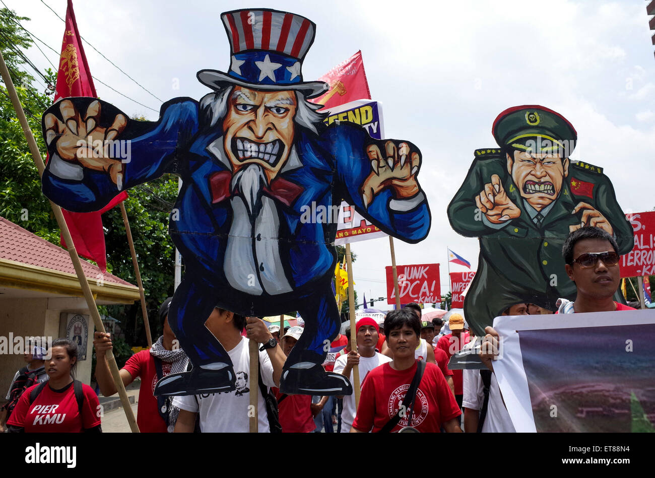 Manila, Philippines. 12th June, 2015. Protesters hold cutouts of the proverbial Uncle Sam and a Chinese general, - Stock Image