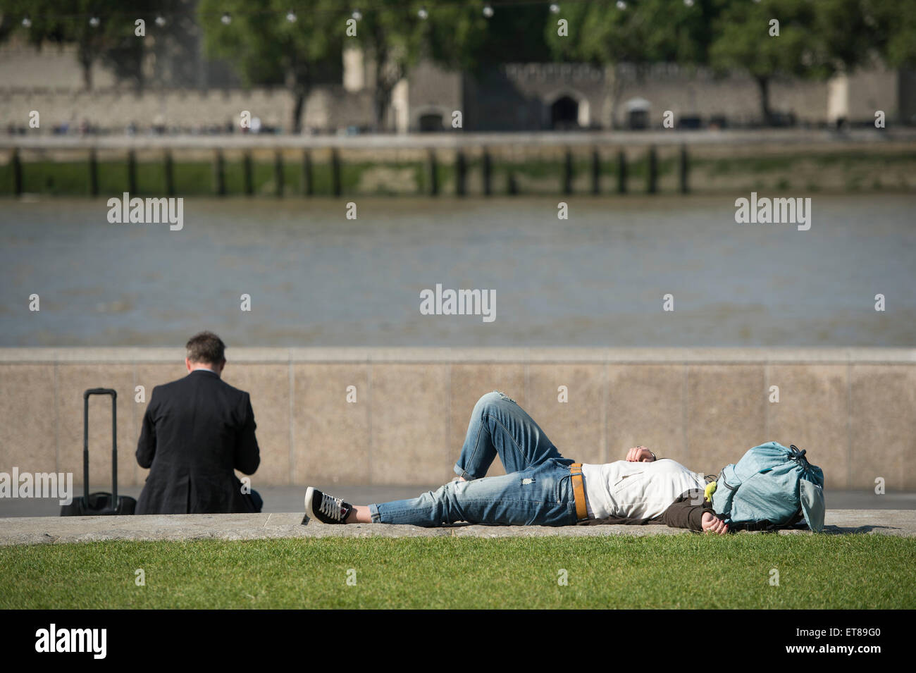 Tourist taking a nap on a sunny day by the River Thames in London - Stock Image