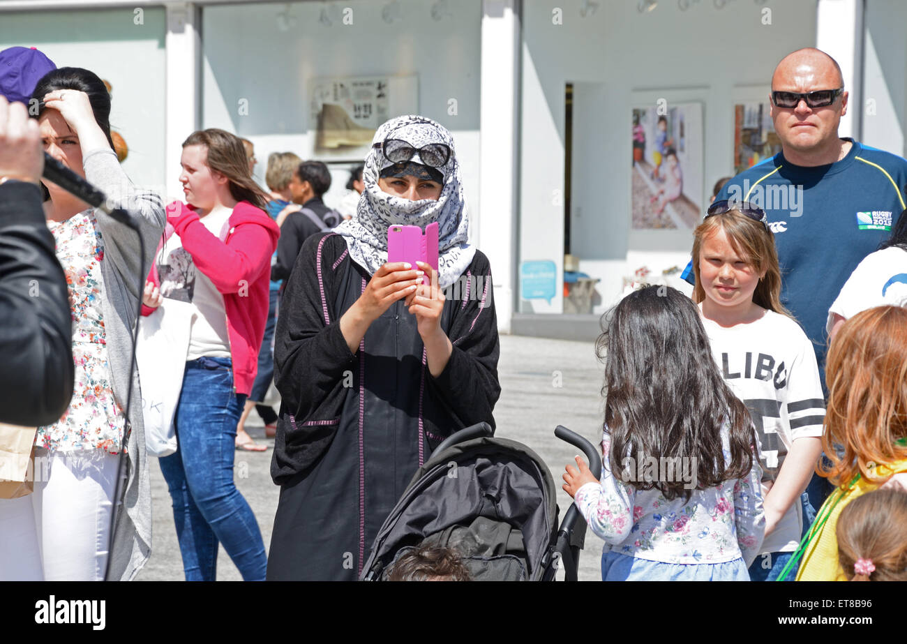 Muslim woman in Niqab in a crowd. Taking photographs on mobile phone. Nottingham, England. - Stock Image