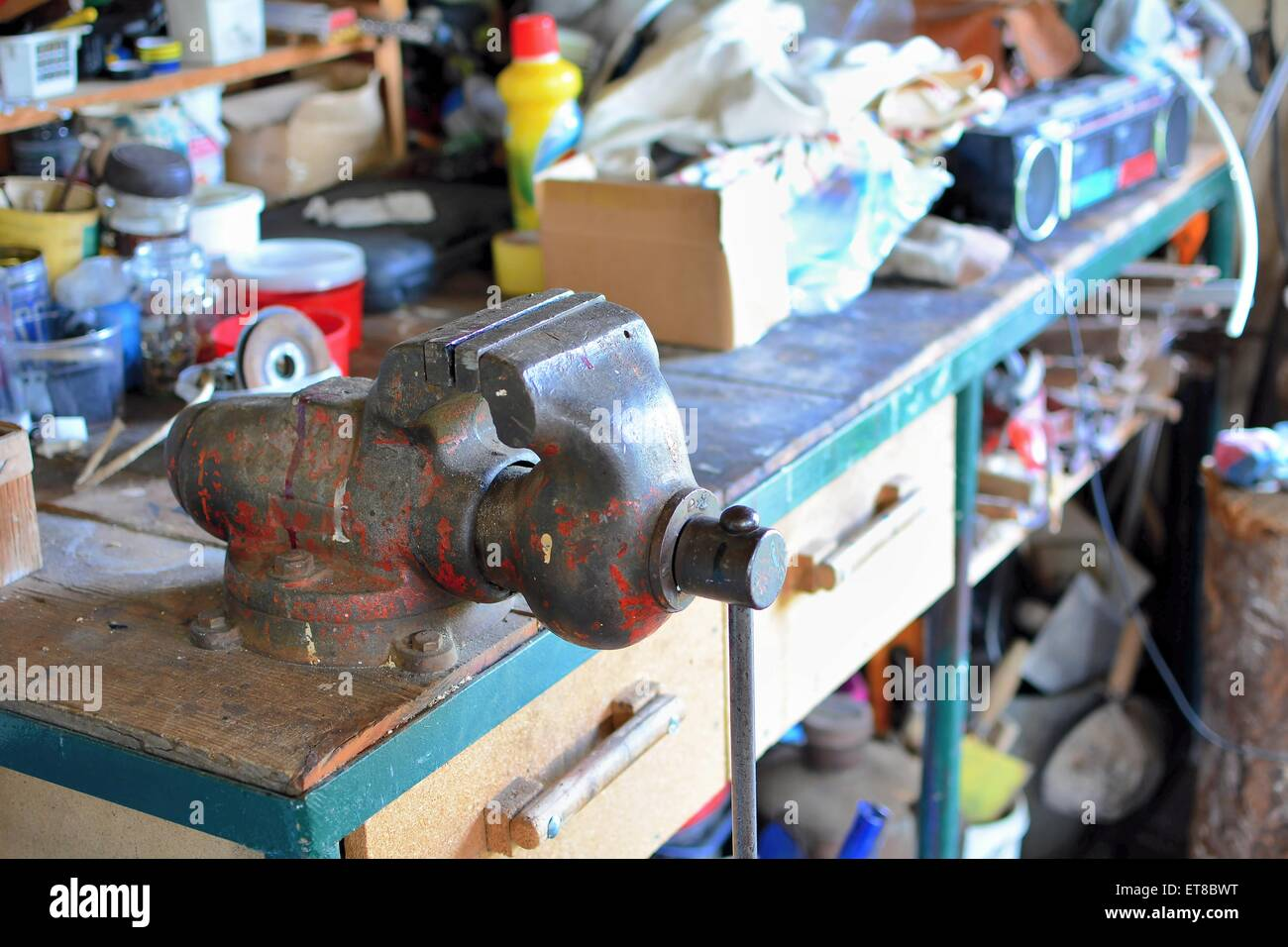 Messy table with old metal rusty vice and other working tools in the workshop. - Stock Image