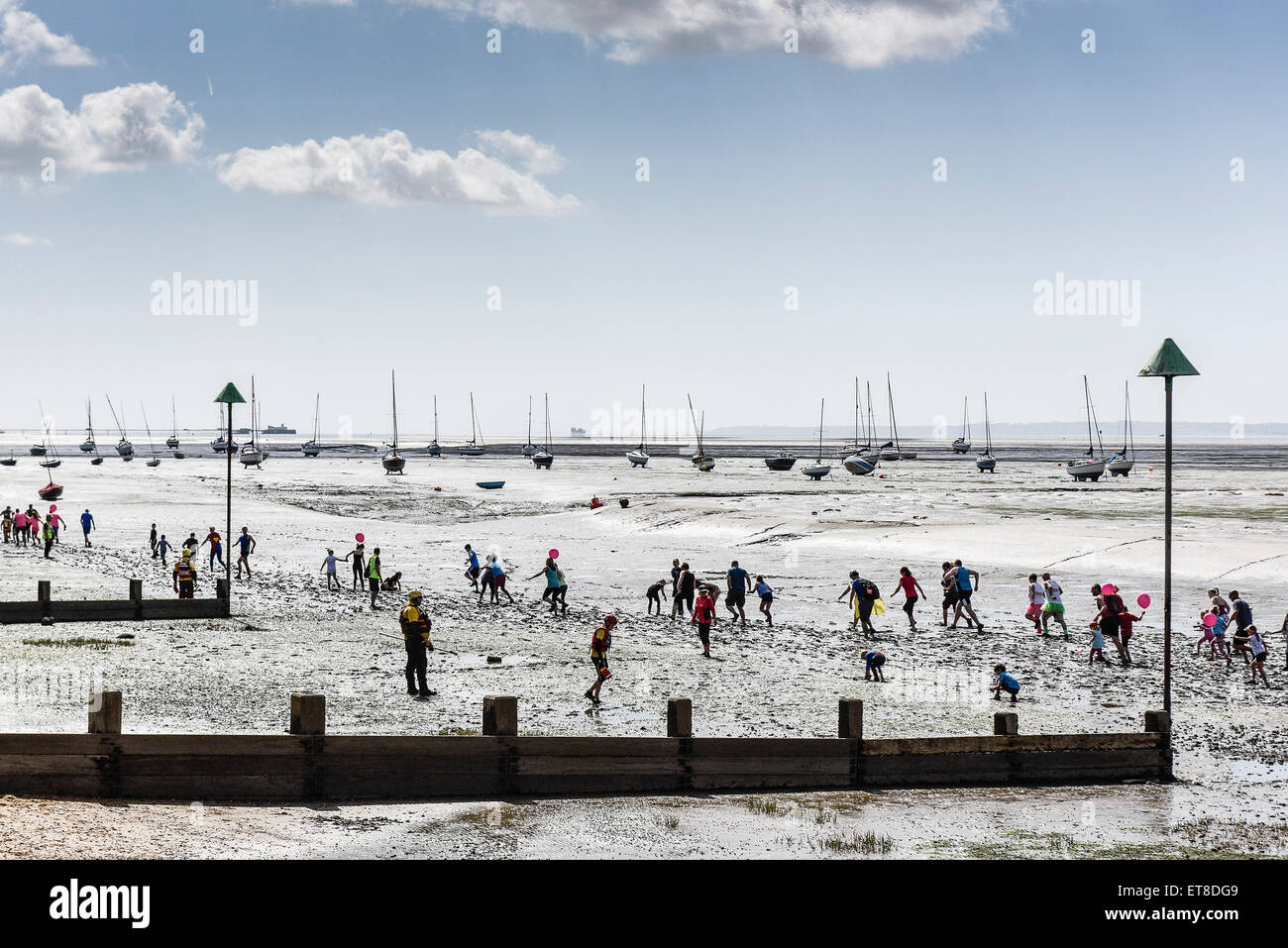 The annual charity fun run across the muddy Thames Estuary foreshore at Leigh on Sea, Essex. - Stock Image