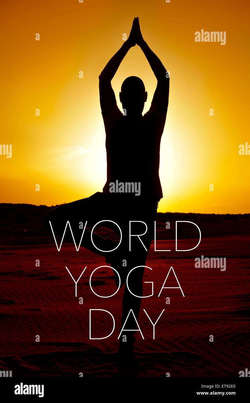 a young yogi man practicing the tree pose outdoors in backlight at sunset and the text world yoga day - Stock Image