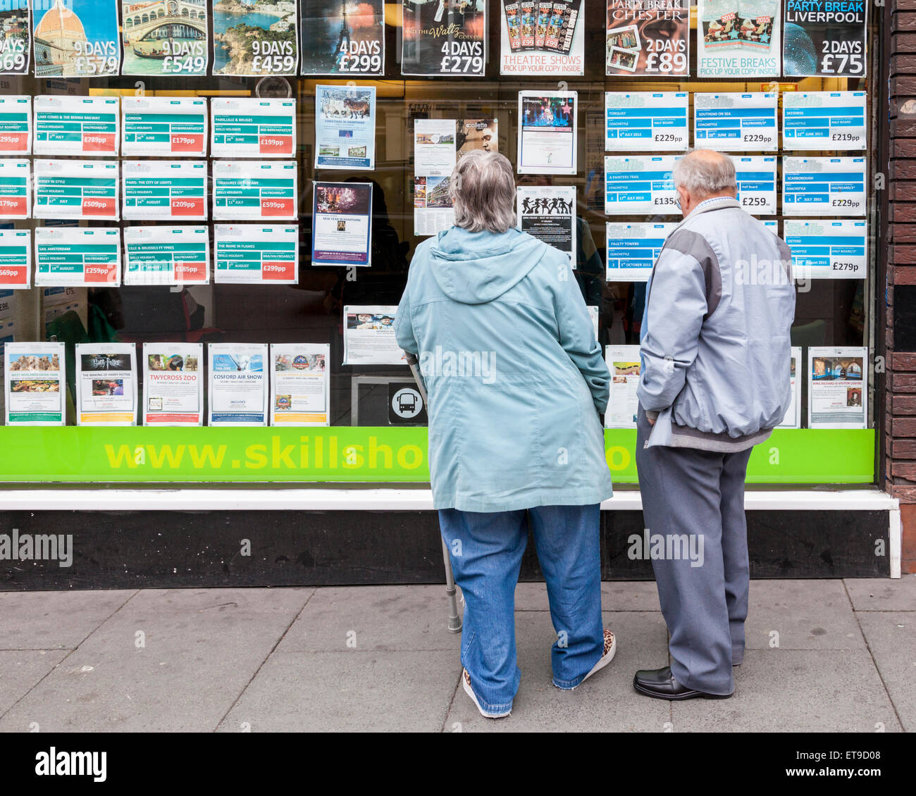 Travel agent's window. Older people looking at holiday information in Skills Holidays travel agency, Nottingham, - Stock Image
