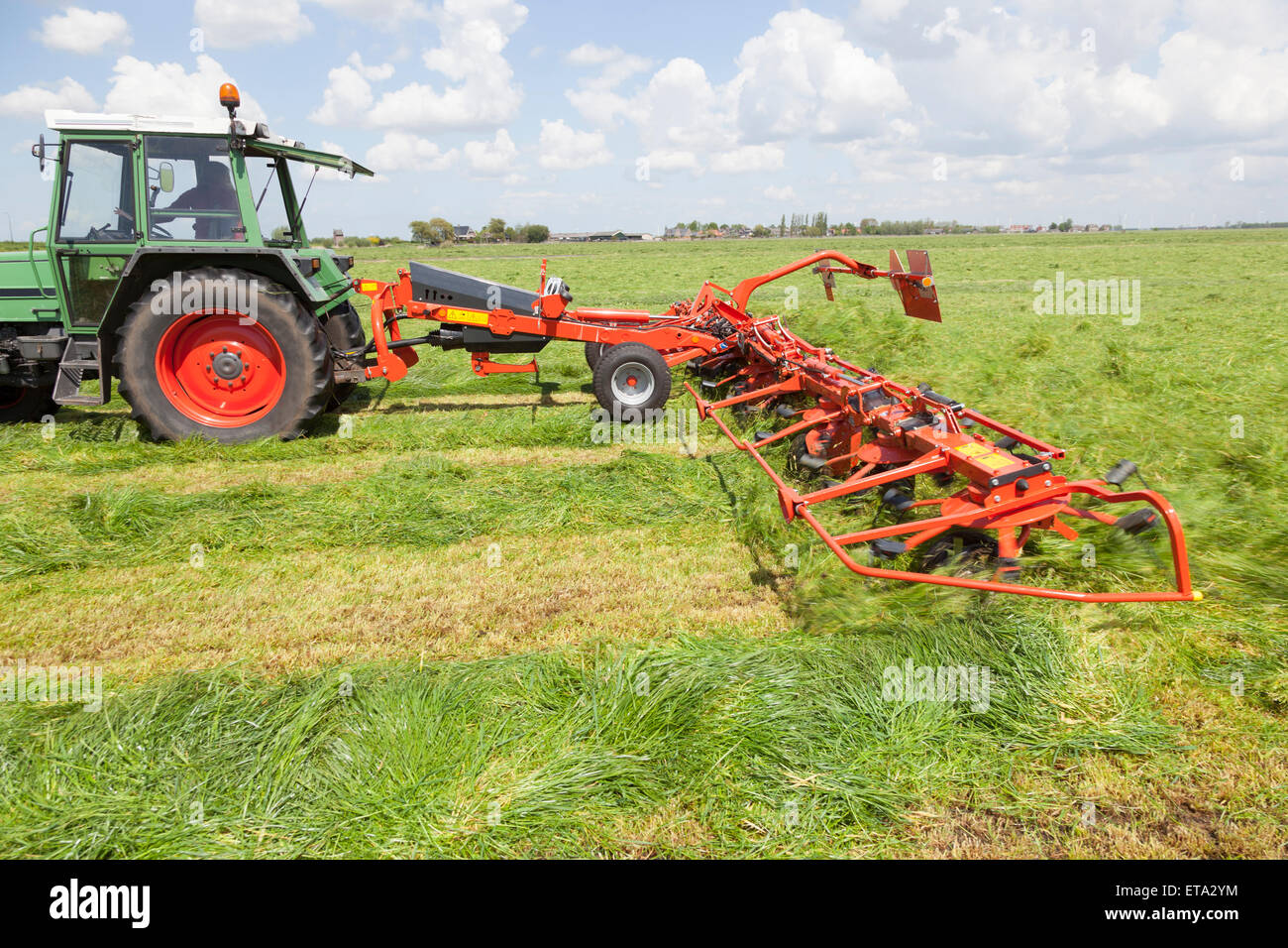red hay turner behind tractor in green meadow in the netherlands - Stock Image