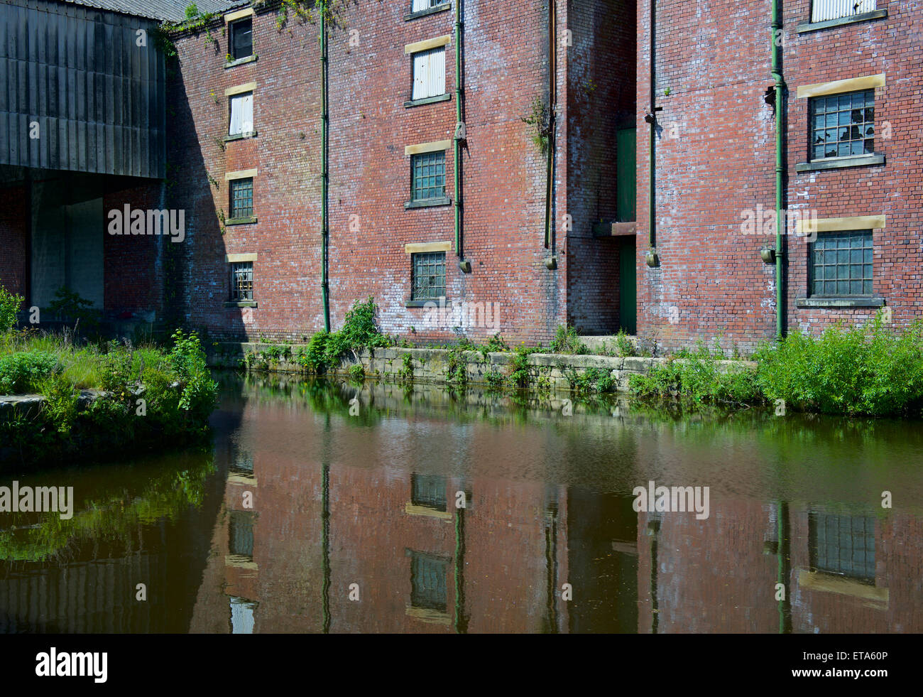 Derelict factory reflected in the Leeds and Liverpool, Canal, Saltaire, West Yorkshire, England UK - Stock Image