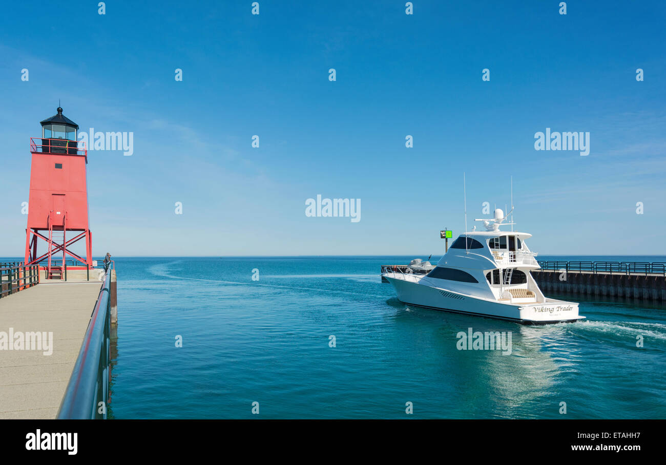 Michigan, Charlevoix, Pine River Channel, powerboat passes historic lighthouse to Lake Michigan - Stock Image