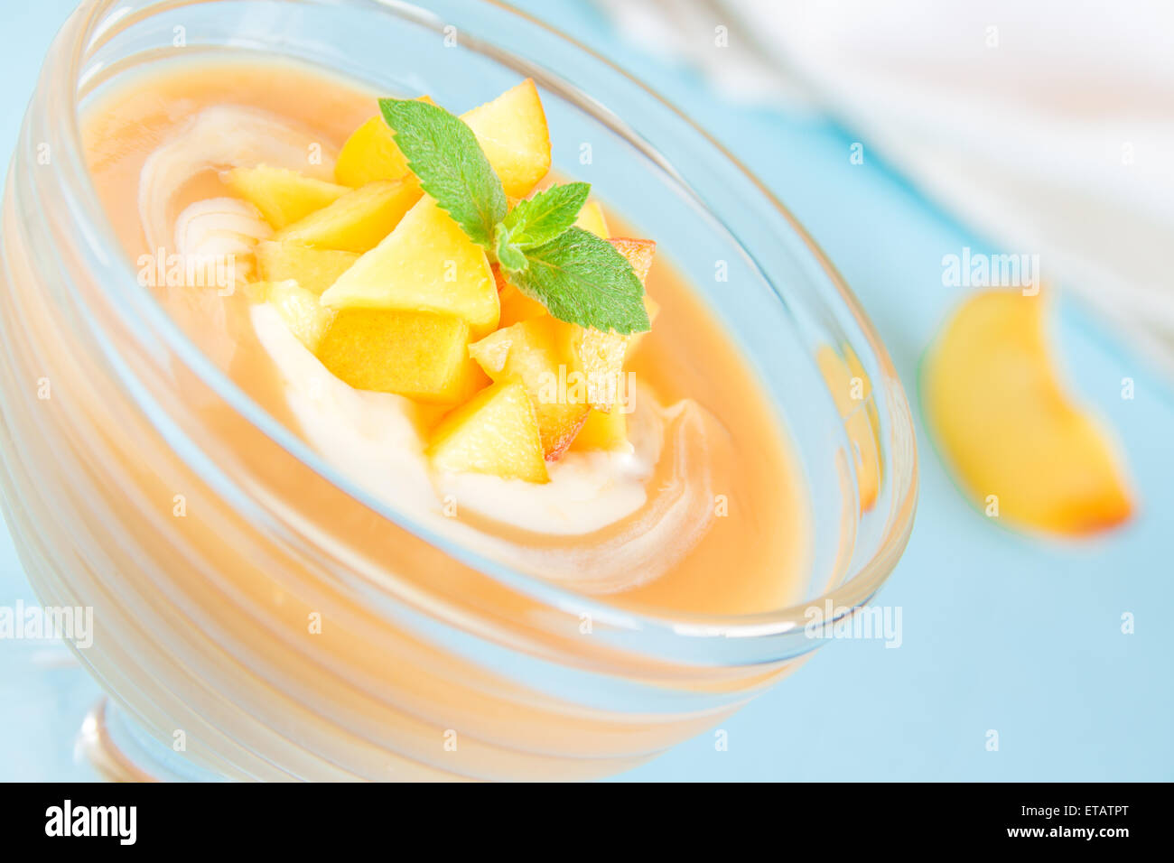 Peach dessert (mousse) with yogurt and mint on blue background - Stock Image
