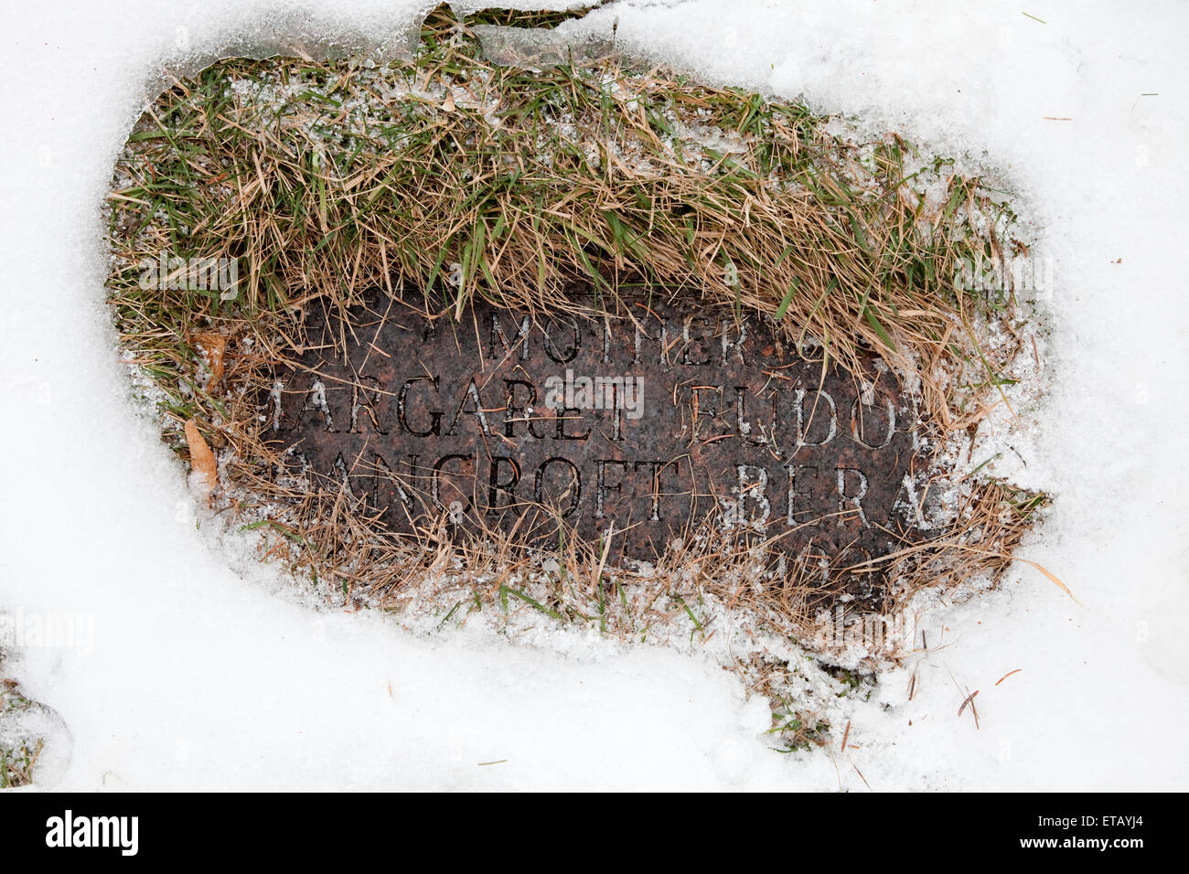 Mother's tombstone cleared of snow and grass to make visible. Lakewood Cemetery Minneapolis Minnesota MN USA - Stock Image