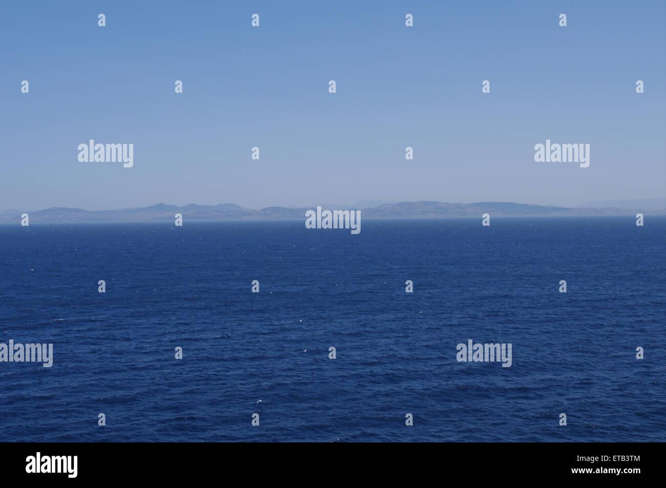 Land emerge from sea mist blue sea sky - Stock Image
