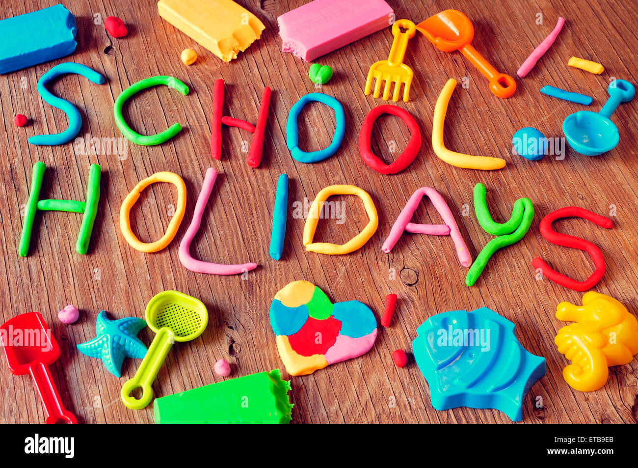the text school holidays made from modelling clay of different colors and some beach toys such as toy shovels and - Stock Image