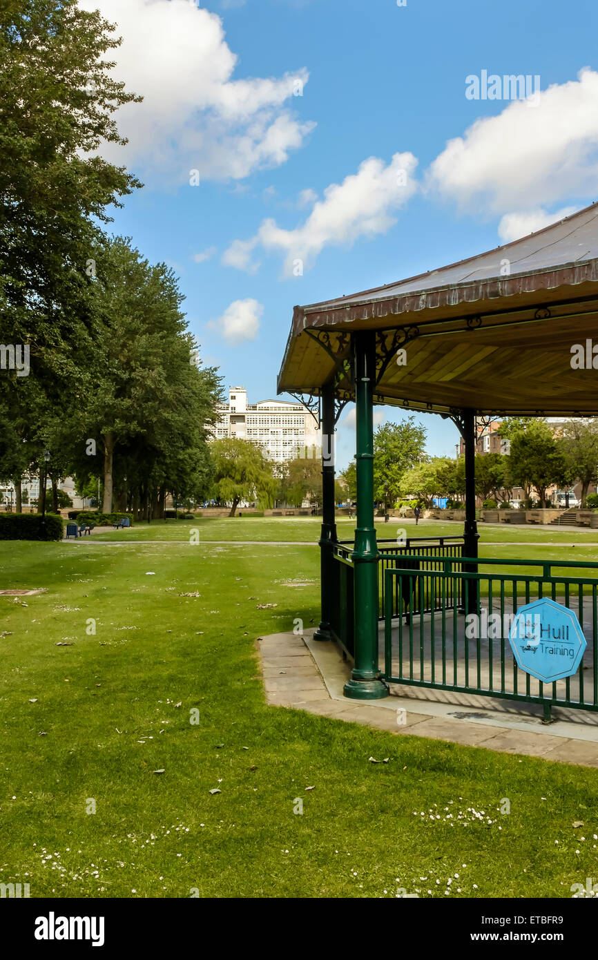 'Hull Training' sign on a bandstand in Queen's Gardens, Hull city centre with Hull College in the background. - Stock Image