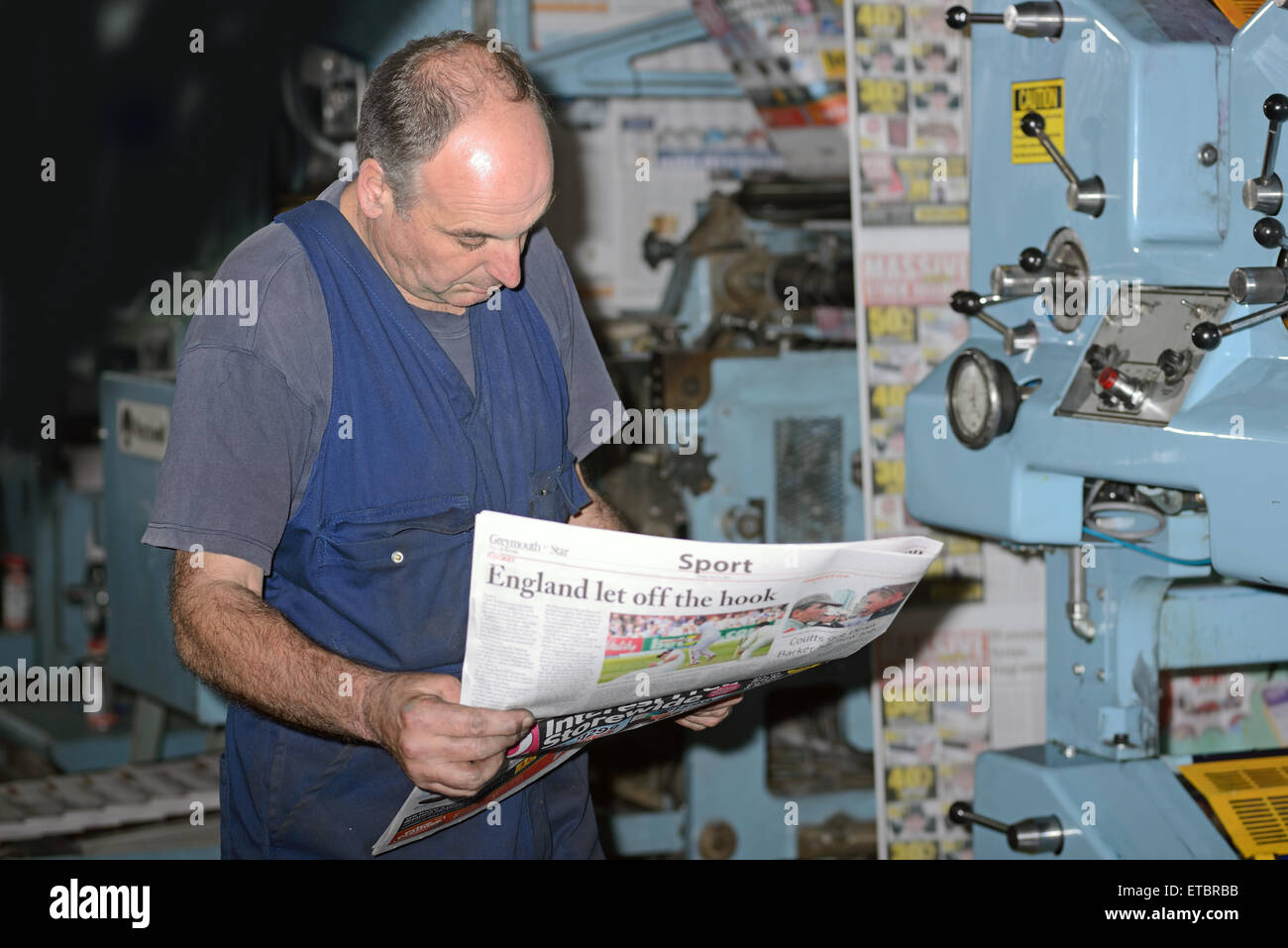 GREYMOUTH, NEW ZEALAND, MAY 22, 2015:  An unidentified printer checks the quality of his workmanship while printing - Stock Image
