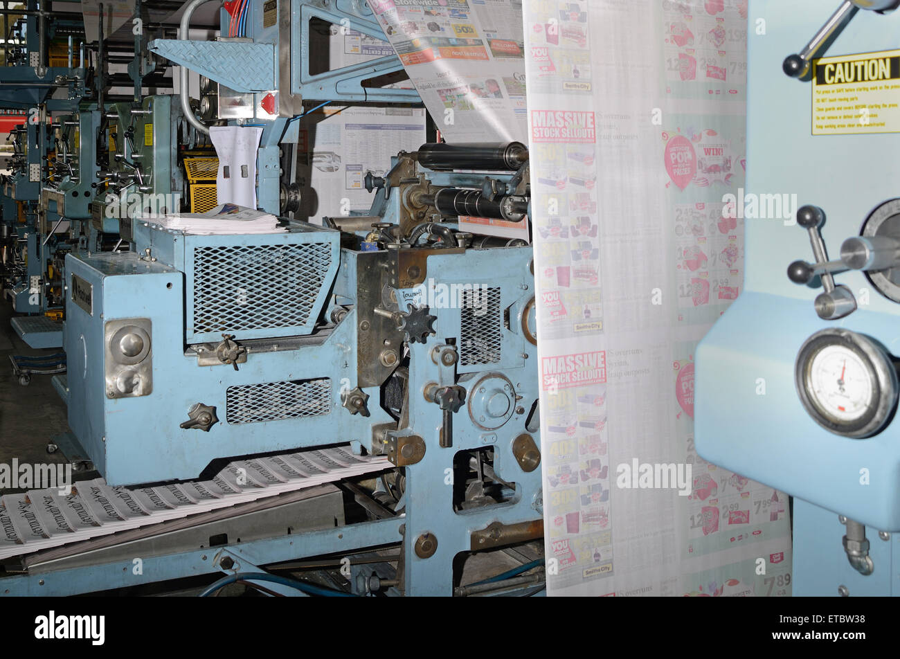 GREYMOUTH, NEW ZEALAND, MAY 22, 2015:  Advertisements dominate the pages  while printing a newspaper - Stock Image