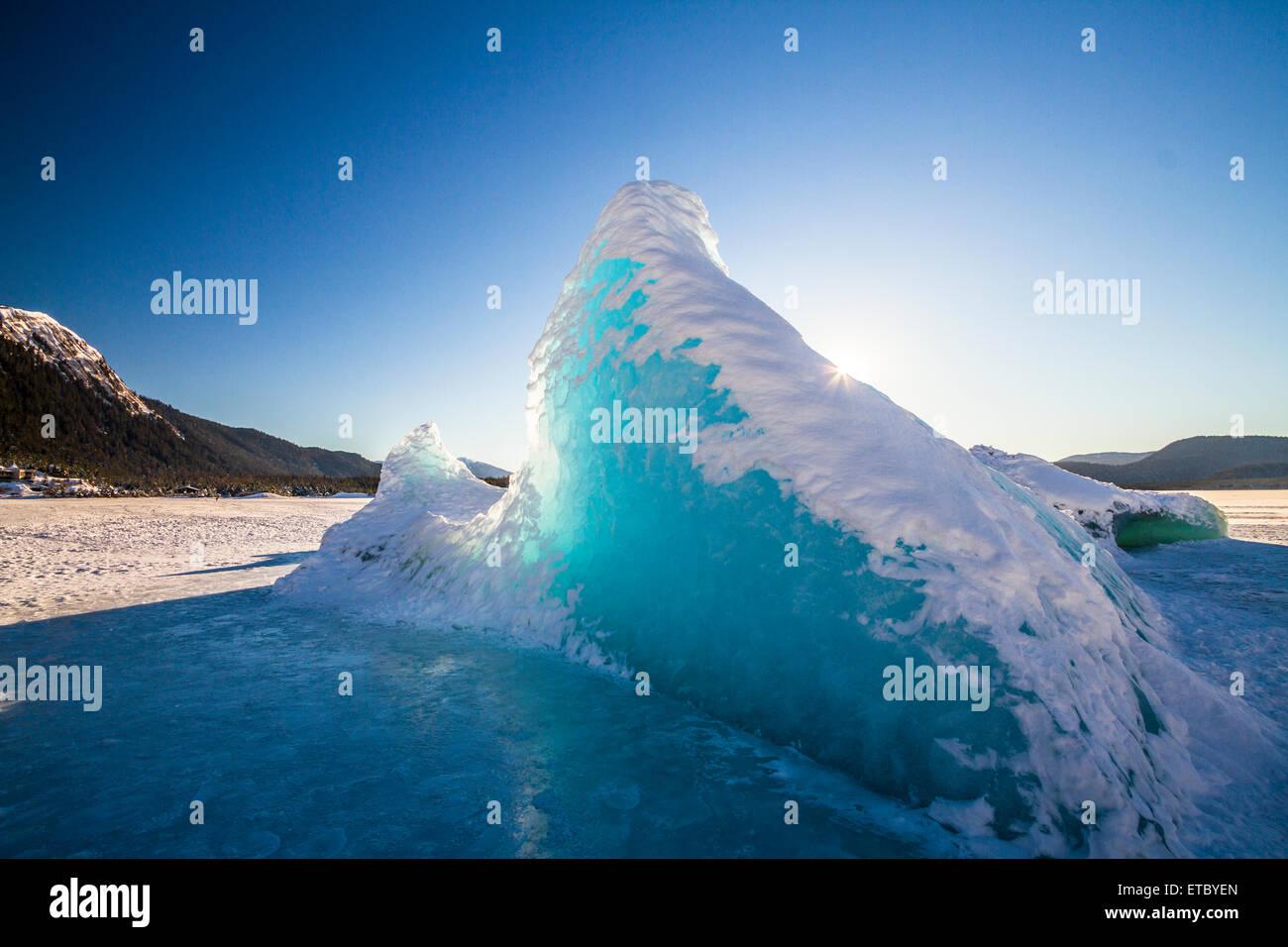 The sun shines through an iceberg on Juneau's frozen Mendenhall glacier, Alaska - Stock Image