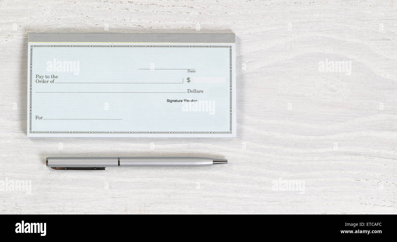 Close up of blank checkbook and silver pen on white wooden desktop. Layout in horizontal format. - Stock Image