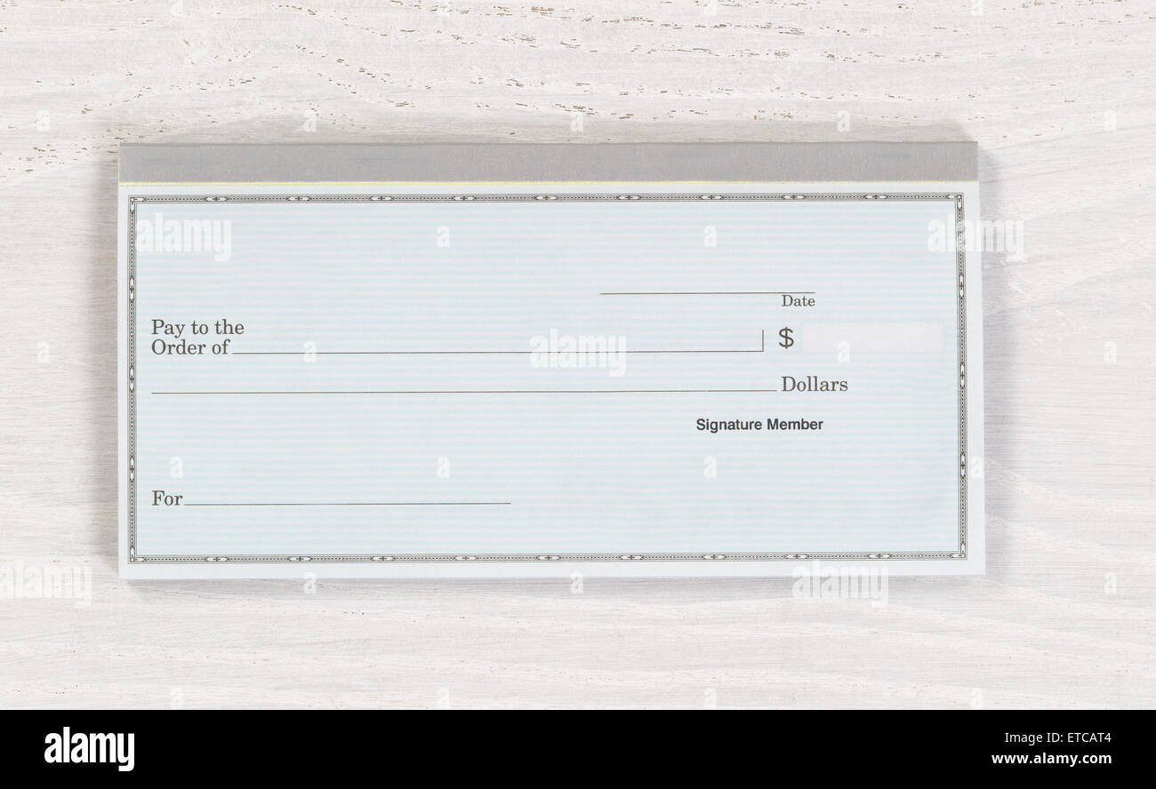 Close up of blank checkbook on white wooden desktop. Layout in horizontal format. - Stock Image