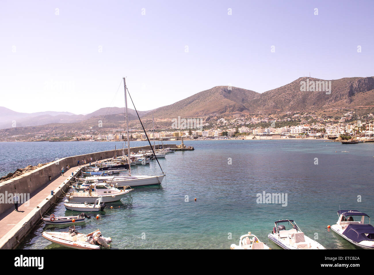 Boats lined up around the harbour in a popular tourist resort of Hersonissos in Crete. - Stock Image