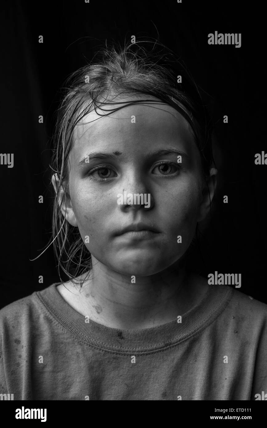 A young girl looking sad and unclean - Stock Image