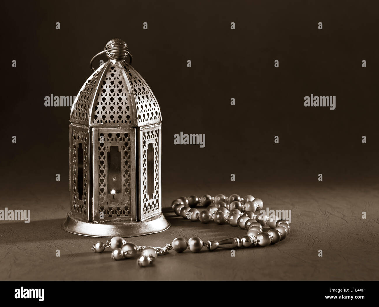 A metallic Ramadan lamp with Islamic rosary beads on black background. Monochromatic image. - Stock Image