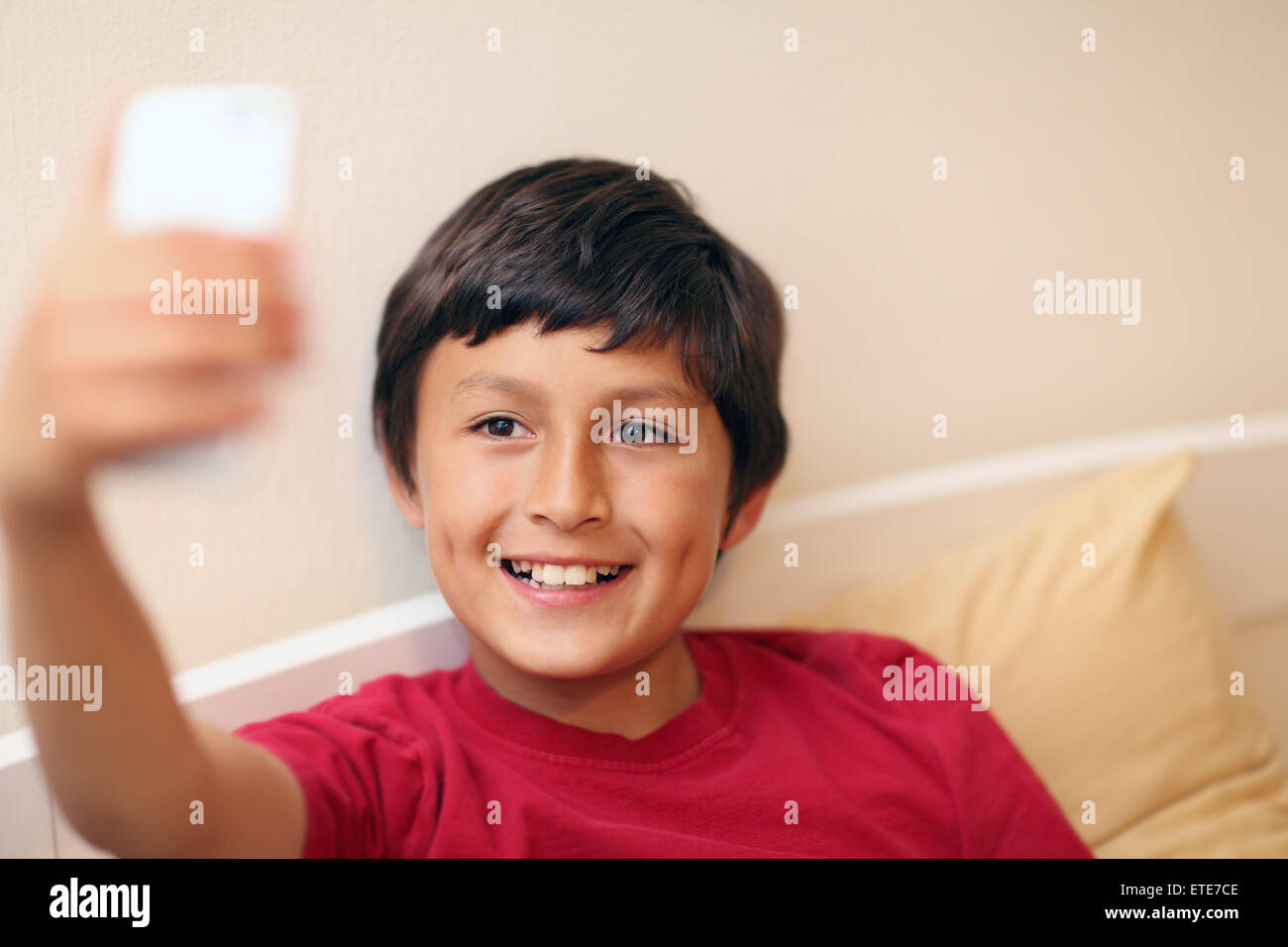 Young boy making selfie pictures with smart phone - with shallow depth of field - Stock Image
