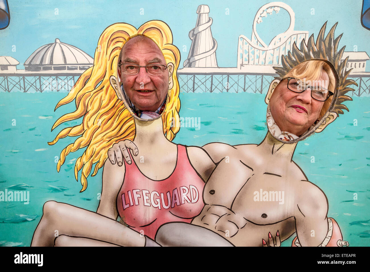 Tourists pose for fun in a cut-out portrait on the Palace Pier, a.k.a. Brighton Pier, in Brighton, East Sussex, - Stock Image