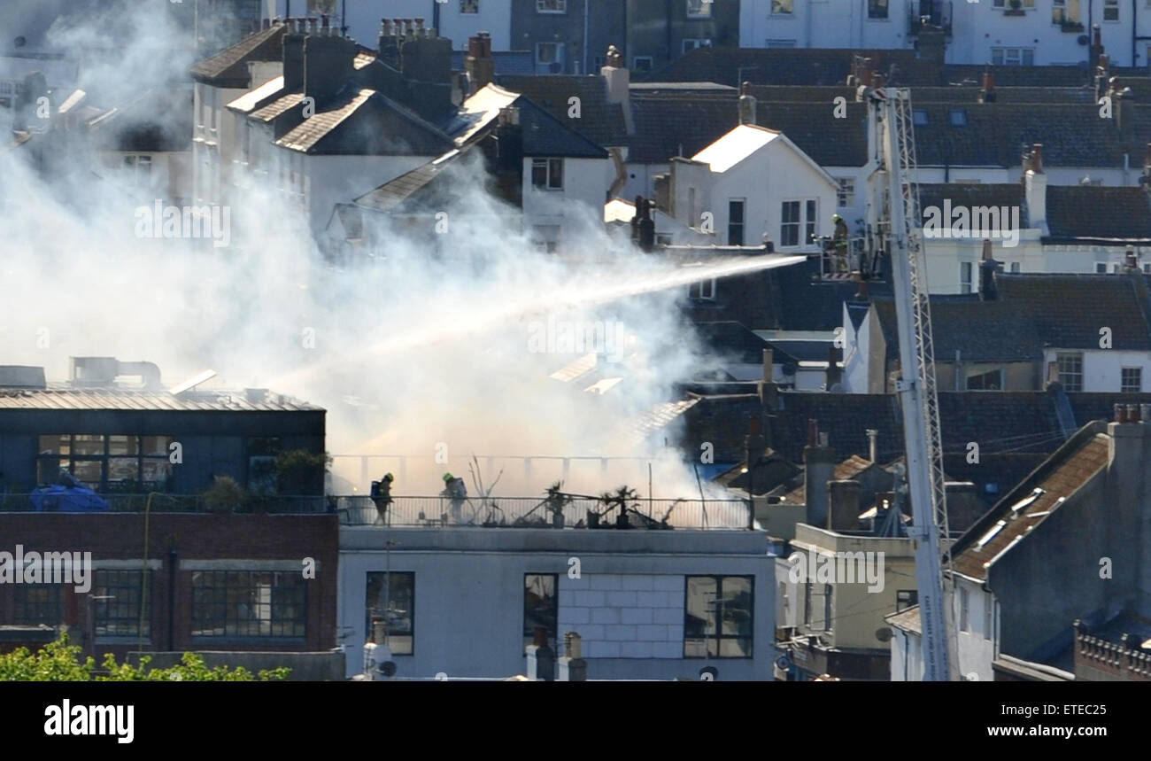 Brighton UK 11th June 2015 - The fire brigade tackle a blaze on the roof of The Argus Lofts flats in the centre - Stock Image