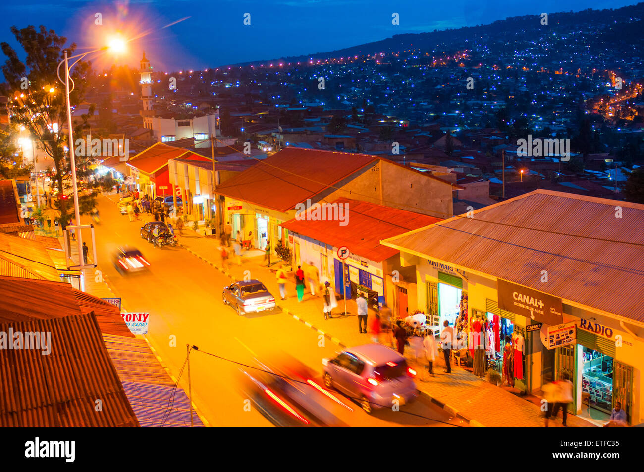 Aerial view of main street - KN 2 Avenue - at dusk, with hillside suburbs beyond, Nyamirambo, Kigali, Rwanda - Stock Image