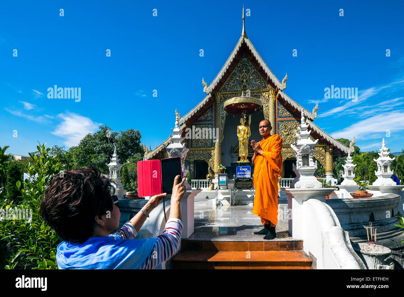 Asia. Thailand, Chiang Mai. Wat Phra Singh. Monk being photographed in front of the golden statue of a revered monk. - Stock Image
