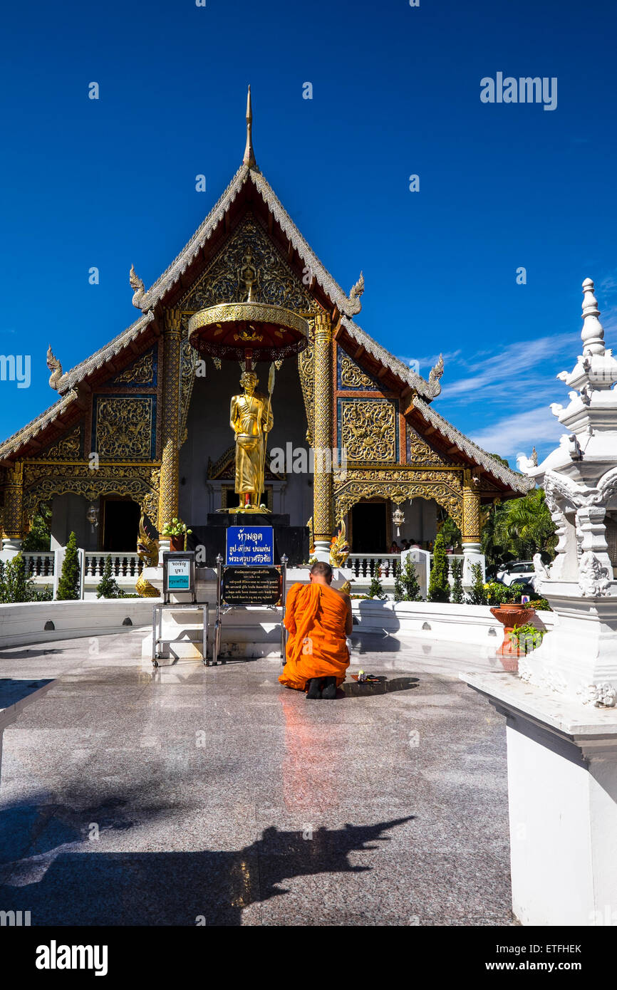 Asia. Thailand, Chiang Mai. Wat Phra Singh. Monk kneeling praying in front of the golden statue of a revered monk. - Stock Image