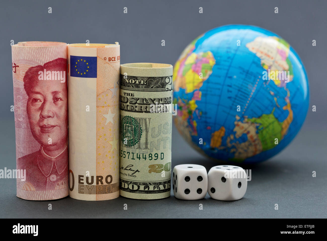 Yuan, euro, and collar next to black and white dice with globe in background.  Game with worldwide risk. - Stock Image